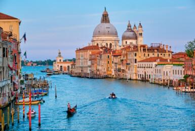 威尼斯大运河全景与贡多拉船和圣玛丽亚德拉礼炮教堂在日落时从 Ponte dell'Accademia 桥。 意大利威尼斯